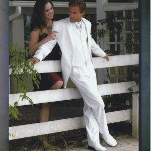 Man wearing white tuxedo leaning against a fence